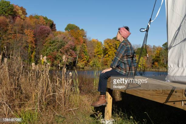 non binary female in 30s sitting lakeside on an autumn day in upstate new york - printed sleeve stock pictures, royalty-free photos & images