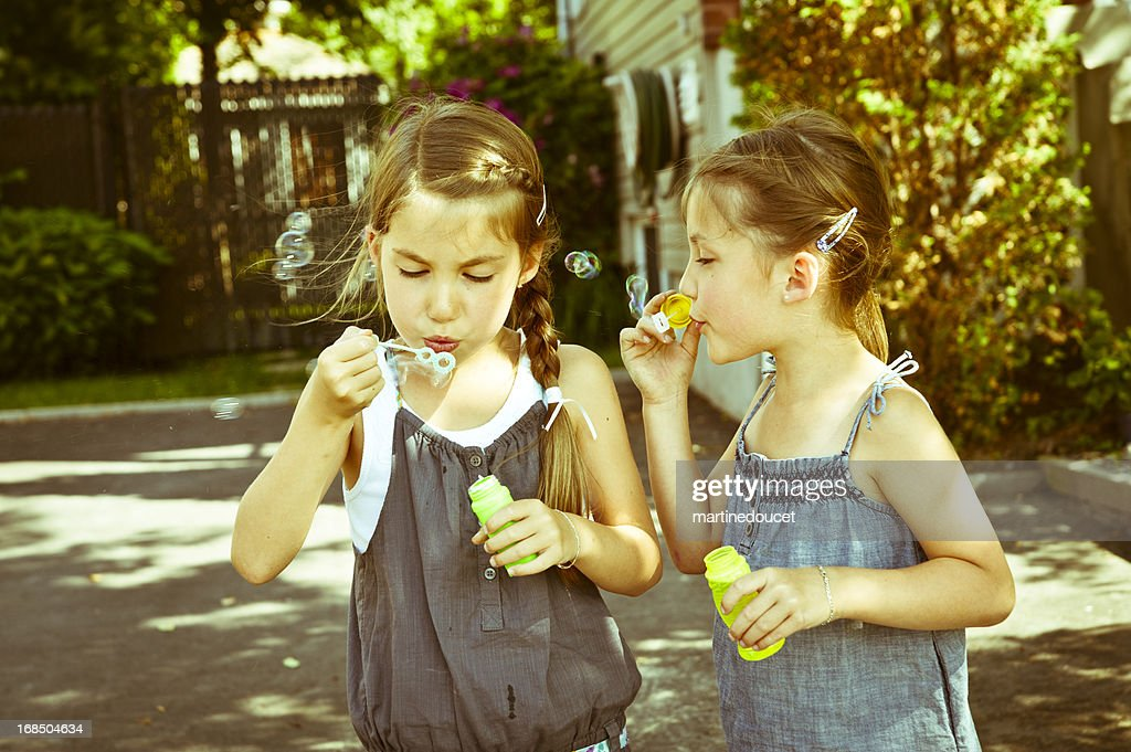 Non identical twins blowing soap bubbles. : Stock Photo