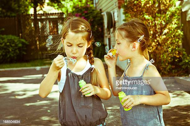 """non identical twins blowing soap bubbles. - """"martine doucet"""" or martinedoucet stock pictures, royalty-free photos & images"""