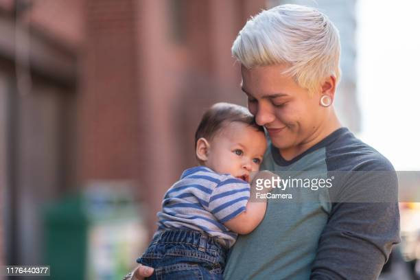 non-binary gender parent with baby - fatcamera stock pictures, royalty-free photos & images