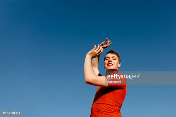 non-binary man in red dress dancing against clear sky - transgender stock pictures, royalty-free photos & images