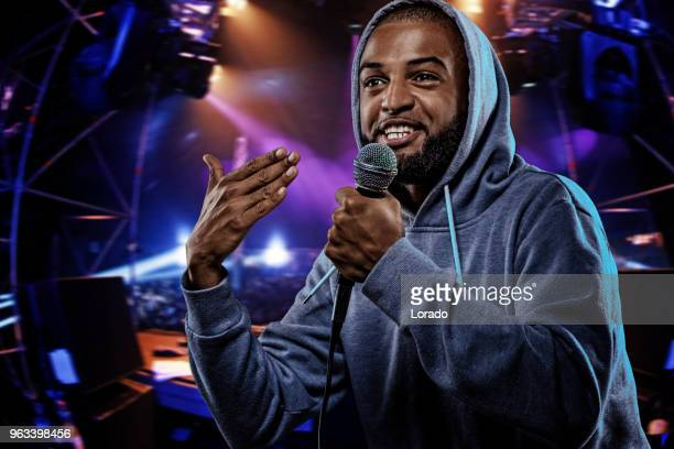 non-caucasian african emcee rapping into a microphone in front of concert lights - rap stock pictures, royalty-free photos & images