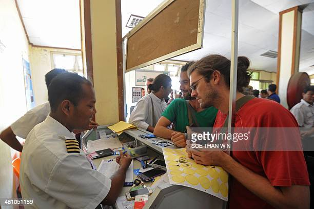 Non-Govermental Organizations staff check in at an airline counter at Sittwe airport, Rakhine state western Myanmar on March 28, 2014. An 11-year-old...