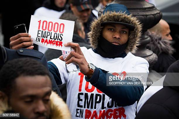 A nonlicensed private hire cab drivers known in France as VTC holds a placard reading '10000 jobs in danger' at the Place de la Nation during a...