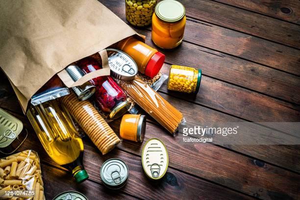 non-perishable foods coming out a paper bag. copy space - saco objeto manufaturado imagens e fotografias de stock