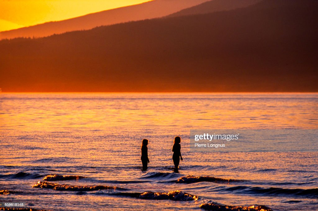 nonrecognizable young girls playing in the sea at sunset, Kitsina Beach, Vancouver, British Columbia, Canada : Stock-Foto