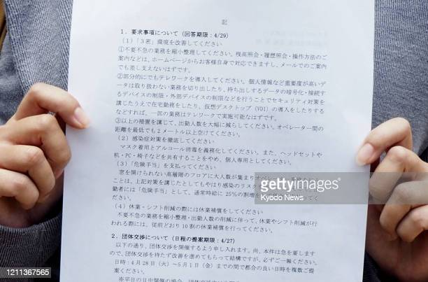 Nonregular employee at a call center in Tokyo holds a plea document on April 24 asking for the employer to strengthen measures against the new...