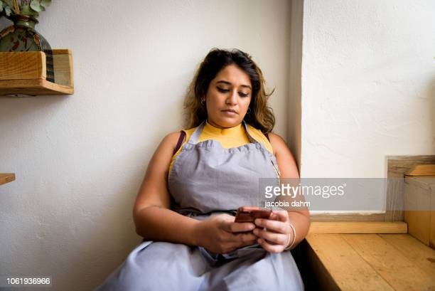 Young chef taking break, sitting on steps, checking mobile phone