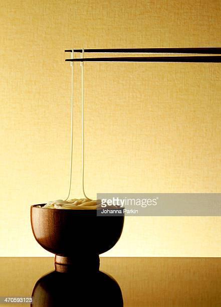 Noodle bowl with 2 chopsticks holding up 2 noodles