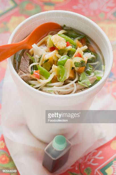 Noodle soup with beef and vegetables in cup, close up