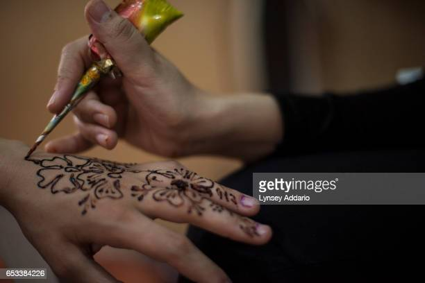 Noor age unknown is painted with traditional henna designs as she prepares for her wedding later that day in a beauty salon in the Zaatari refugee...