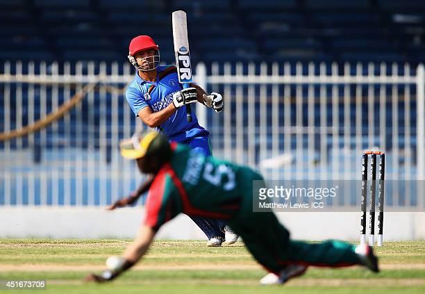 Noor Ali Zadran of Afghanistan hits the ball past Steve Tikolo of Kenya during the ICC World Twenty20 Qualifier between Afghanistan and Kenya at...