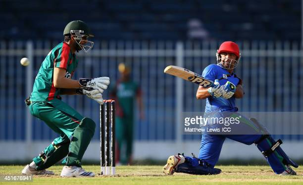 Noor Ali Zadran of Afghanistan plays a reverse sweep shot as Morris Ouma of Kenya looks on during the ICC World Twenty20 Qualifier between...