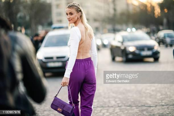 Noor de Groot, Queen of Jet Lags, wears a backless white top, purple sport pants, a purple Fendi bag, outside Rochas, during Paris Fashion Week...