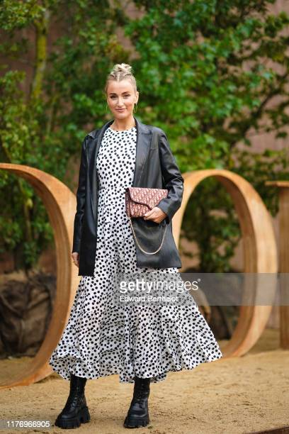 Noor de Groot wears large earrings a black leather jacket a white dress with printed polka dots a Dior monogram logo bag wears outside Dior during...