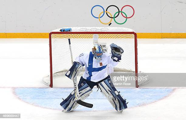 Noora Raty of Finland raises her glove as a puck passes over the net in the first period against Germany during the Women's Ice Hockey Classification...