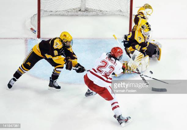 Noora Raty of the Minnesota Gophers blocks a shot by Hilary Knight of the Wisconsin Badgers as Kelly Seeler of the Minnesota Gophers assists in...