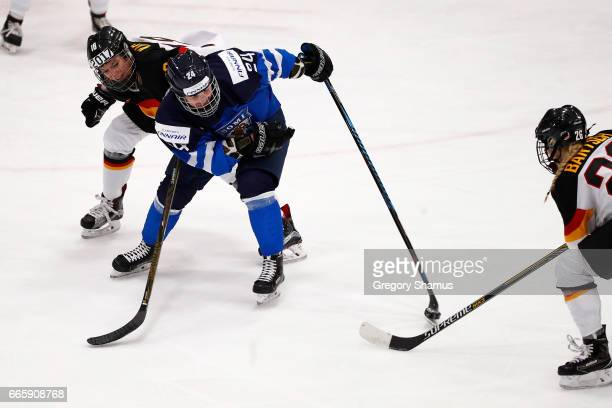 Noora Tulus of Finland tries to control the puck between Bernadette Karpf and Anne Bartsch of Germany during the first period in the bronze medal...