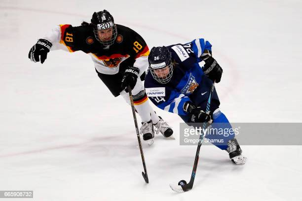 Noora Tulus of Finland tries to control the puck in front of Bernadette Karpf of Germany during the first period in the bronze medal game at the 2017...