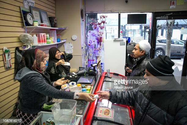 Nooraisha and her cousin Aisha tend to customers at the Shwe Myanmar Grocery Store on January 11 2019 in Chicago Illinois Nooraisha and her family...