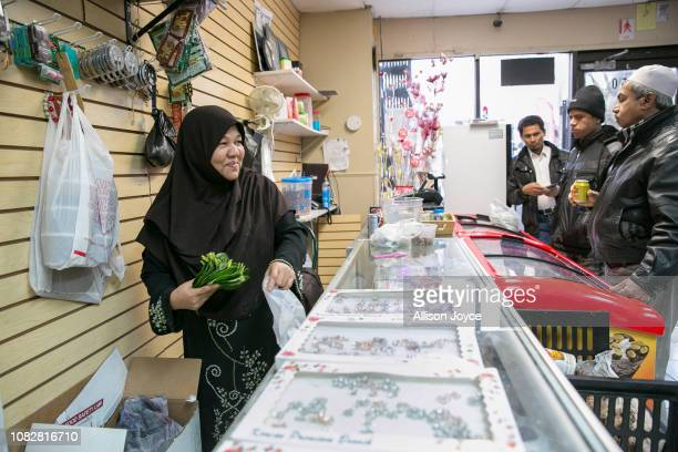 Nooraisha tends to customers at her store the Shwe Myanmar Grocery Store on January 11 2019 in Chicago Illinois Nooraisha and her family escaped...