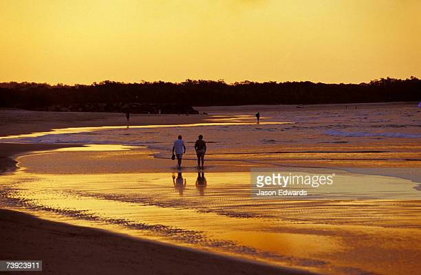 A couple going for a romantic walk on the beach at sunset.