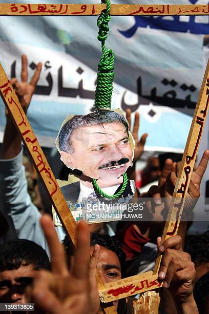 A noose is put around the neck of a picture of embattled Yemeni President Ali Abdullah Saleh during an antiregime rally in Sanaa on January 12 2012...