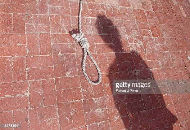 a noose rests on a brick floor by a man's shadow. - noose stock photos and pictures