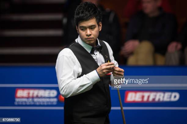 Noppon Saengkham of Thailand chalks the cue during his first round match against Neil Robertson of Australia on day six of Betfred World Championship...