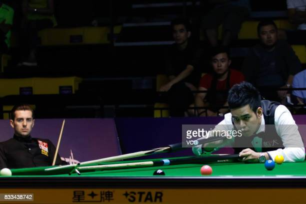Noppon Saengkham of Thailand plays a shot during his first round match against Mark Selby of England on day two of Evergrande 2017 World Snooker...