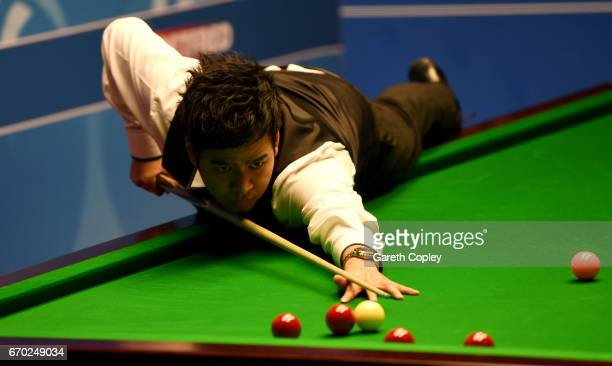 Noppon Saengkham plays a shot against Neil Robertson during their first round match of the World Snooker Championship at Crucible Theatre on April 19...