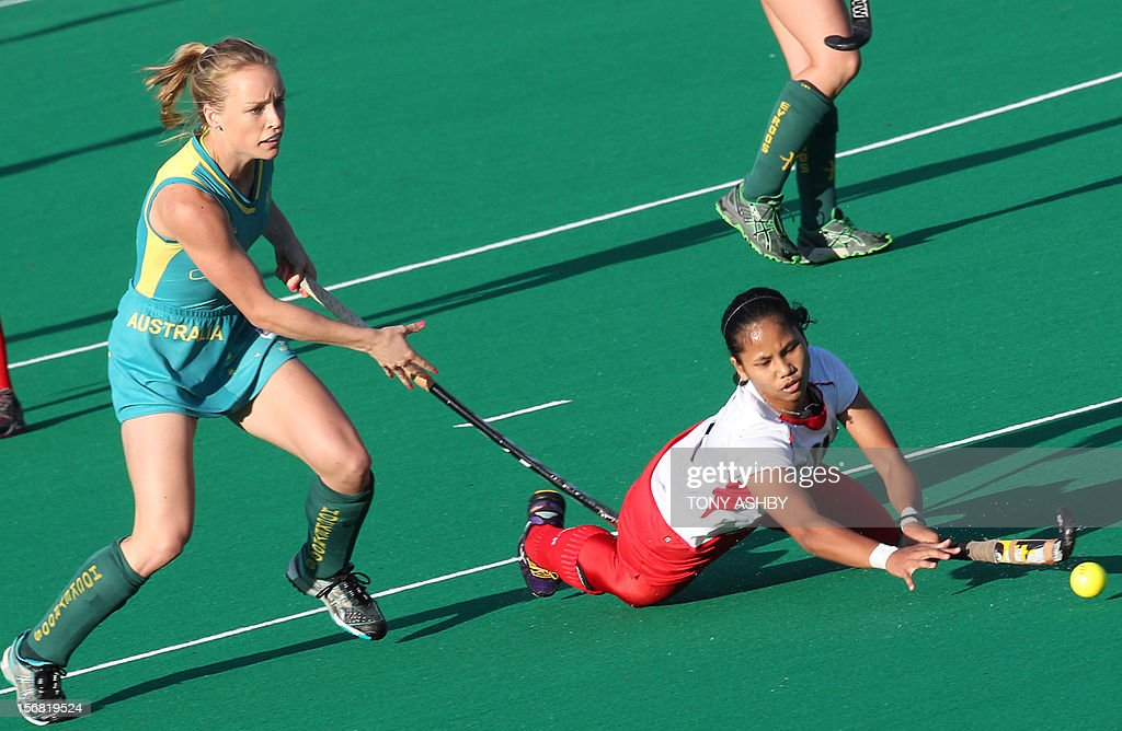 Nor Azlin Sumantri (R) of Malaysia dives for the ball near Jane-Anne Claxton (L) of Australia during their women's Under 21's match at the International Super Series hockey tournament in Perth on November 22, 2012. Australia won 3-2.