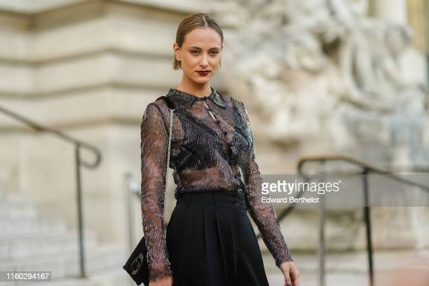 Nora Arnezeder wears a glittery bead embroidered black transparent shirt a black bag black widelegs pants outside Armani during Paris Fashion Week...