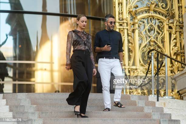 Nora Arnezeder wears a glittery bead embroidered black transparent shirt black widelegs pants black pointy heeled pumps A guest wears sunglasses a...