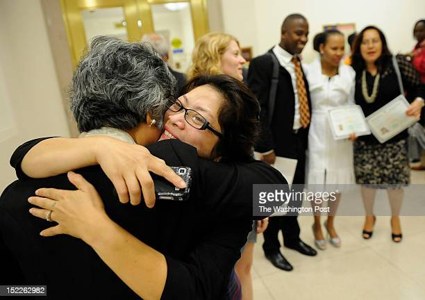 Nora Gutierrez, left, is hugged by friend Genalin Panlaqui, center, following a naturalization ceremony where Nora was one of 215 people to become a...