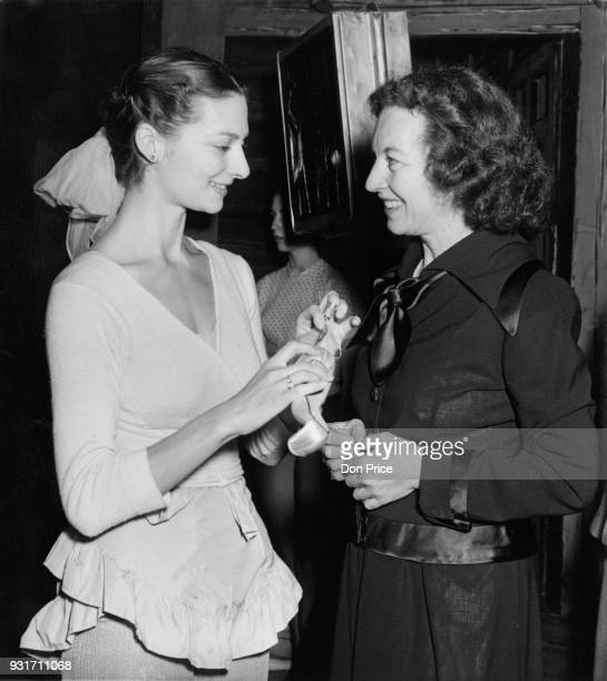 Nora Kaye , prima ballerina of the American Ballet Theatre talks to Lucia Chase , director of the company, during a break at the Empire Theatre in...