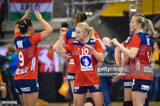 Nora Mork Stine Bredal Oftedal and Heidi Loke of Norway celebrate scoring a point during IHF Women's Handball World Championship group B match...