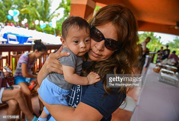 Nora SandigoOtero hugs 5 month old Carlos Hernandez during a luncheon for children that she holds guardianship over on June 7 2014 in Miami Fl...