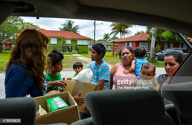 Nora SandigoOtero left delivers emergency food relief to Leticia Ramires far right holding her 5 monthold granddaughter Cristina Beltran Maria...