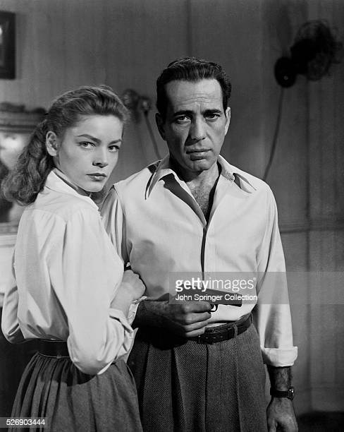 Nora Temple holds Frank McCloud's arm as he grips a pistol.