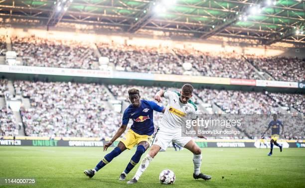 Nordi Mukiele of Leipzig challenges Thorgan Hazard of Moenchengladbach during the Bundesliga match between Borussia Mönchengladbach and RB Leipzig at...