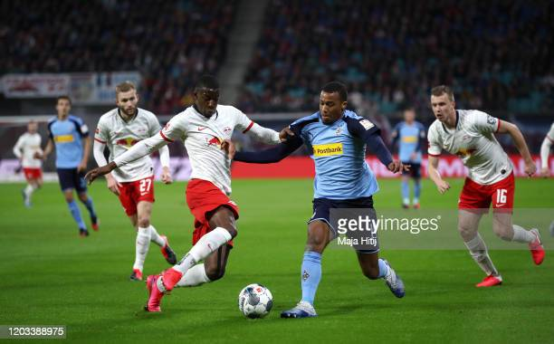 Nordi Mukiele of RB Leipzig battles for possession with Alassane Plea of Borussia Monchengladbach during the Bundesliga match between RB Leipzig and...