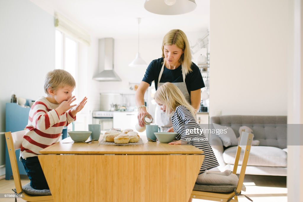 Nordic family eating semla buns on Shrove Tuesday : Stock Photo