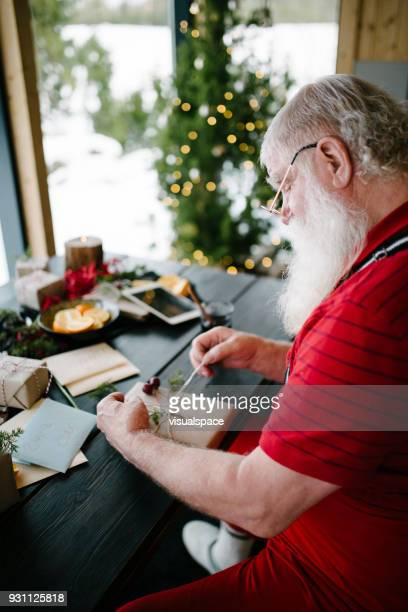 Nordic Santa Claus wrapping presents in his living room