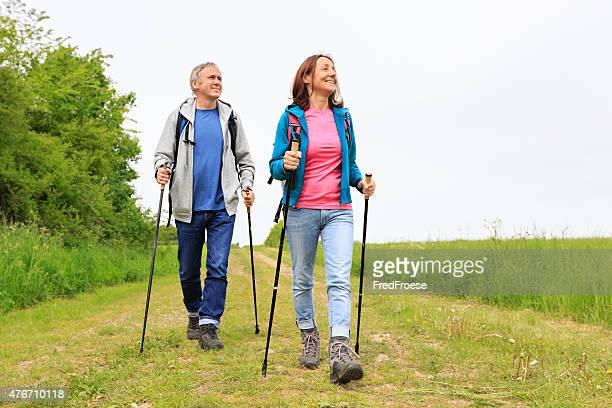 Caminata nórdica activa pareja madura disfrutando de excursionismo