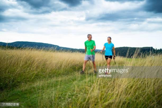 nordic walking reife serge paar - aktiver lebensstil stock-fotos und bilder