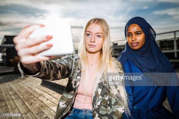 nordic youth lifestyle - verschiedene teens machen selfie - zurückhaltende kleidung stock-fotos und bilder