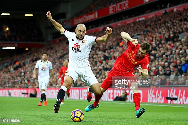 Nordin Amrabat of Watford and James Milner of Liverpool battle for possession during the Premier League match between Liverpool and Watford at...