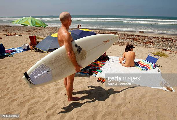 Noreen Crane right of Costa Mesa relaxes nude as her husband Dennis Crane holds his surfboard at the nude section of trail 6 in San Onofre State...
