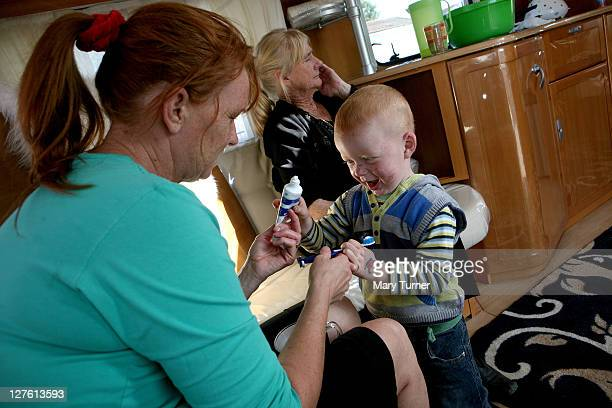 Noreen Sheridan helps her son Pat in their caravan at Dale Farm on September 23 2011 near Basildon England Hundreds of travellers remain under threat...